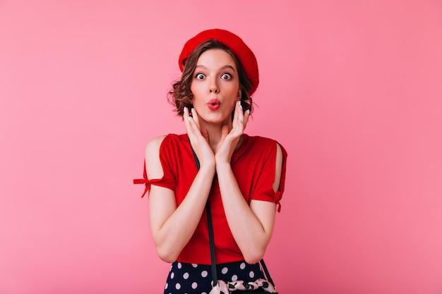 Cudowna biała dziewczyna w czerwonej bluzce pozuje z całowaniem wyrazem twarzy. romantyczna francuska kobieta w pozycji bered.