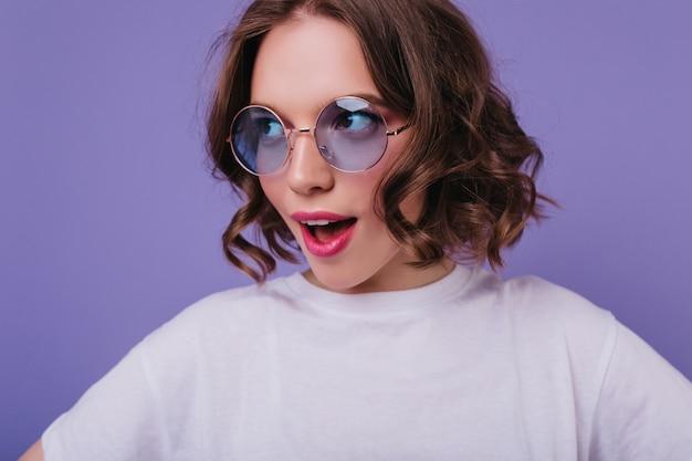Cudowna biała dziewczyna z modną fryzurą pozuje z delikatnym uśmiechem na fioletowej ścianie. inspirowana modelka nosi eleganckie okulary przeciwsłoneczne.