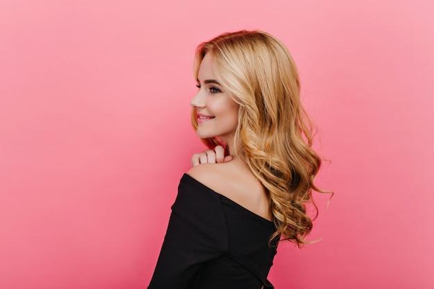 Cudowna blada dziewczyna z elegancką kręconą fryzurą, odwracając wzrok. strzał z tyłu zadowolonej jasnowłosej kobiety w czarnym ubraniu.
