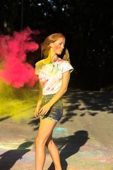 Cudowna blondynka świętująca festiwal holi różową i żółtą suchą farbą