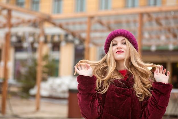 Cudowna blondynka z długimi włosami pozuje na ulicy w kijowie