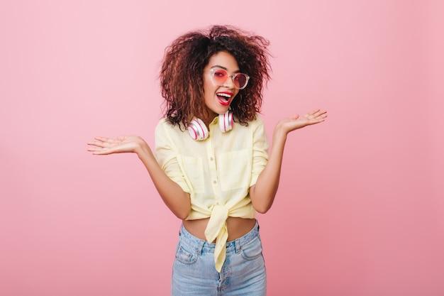 Cudowna brunetka kobieta z kręconymi fryzurami pozuje z delikatnie uśmiechem w modnej żółtej koszuli. kryty portret pewnej siebie stylowej afrykańskiej dziewczyny o ciemnobrązowych włosach.
