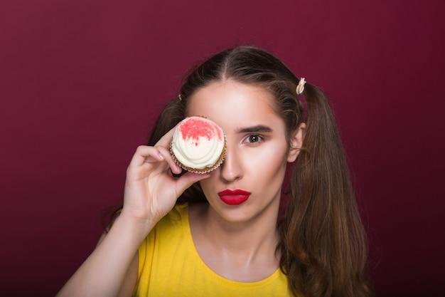 Cudowna brunetka z jasnym makijażem trzymająca sernik w pobliżu oczu