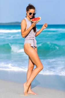 Cudowna ciemnowłosa dziewczyna w okularach przeciwsłonecznych, pozowanie w nadmorskim kurorcie w letnie wakacje. zewnątrz portret brunetka modelka trzymając arbuza i patrząc na tle oceanu.