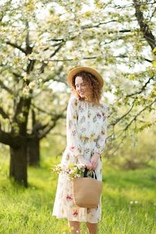 Cudowna dziewczyna chodzi po kwitnącym wiosennym ogrodzie. pojęcie jedności człowieka z naturą.