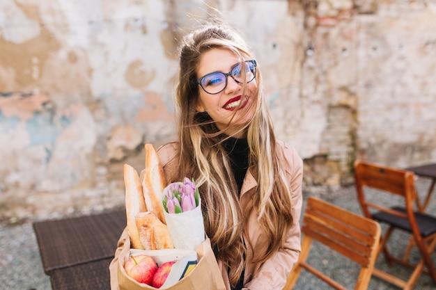 Cudowna dziewczyna po sesji zdjęciowej kupiła świeże jedzenie i pije kawę ciesząc się słonecznym dniem. stylowa młoda kobieta fotograf trzymając torbę na zakupy i filiżankę cappuccino, pozowanie w kawiarni na świeżym powietrzu.