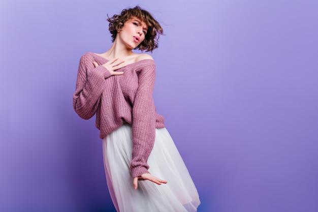 Cudowna dziewczyna w bujnej spódnicy vintage tańczy podczas sesji zdjęciowej. zdjęcie zadowolonej modelki kaukaski z krótkimi ciemnymi włosami, pozowanie na jasnej ścianie.