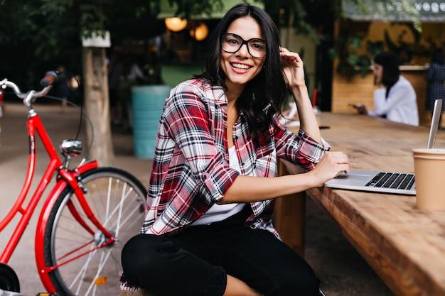Cudowna dziewczyna w dobrym nastroju siedzi na mieście z laptopem i uśmiecha się. zewnątrz portret atrakcyjna brunetka dama w okularach pozuje obok roweru.