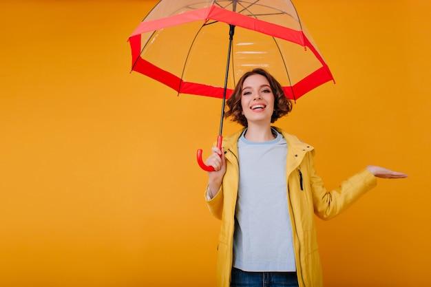 Cudowna dziewczyna w dobrym nastroju, śmiejąca się z czerwonym parasolem. wewnętrzne zdjęcie modnej rasy kaukaskiej z błyszczącym makijażem podczas sesji zdjęciowej z parasolką.