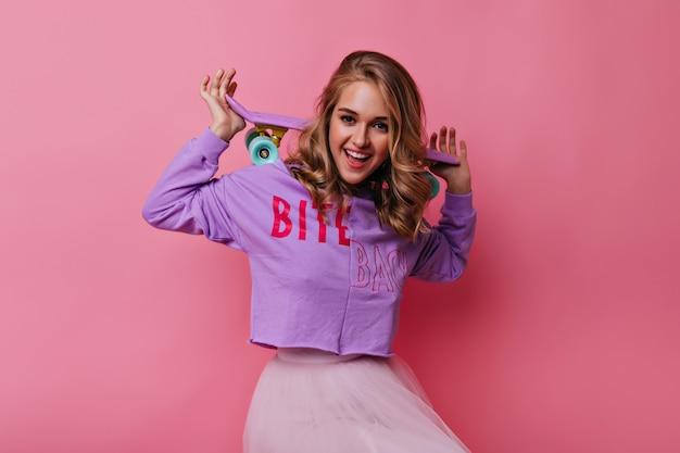 Cudowna dziewczynka kaukaski pozuje z radosnym uśmiechem na pastelowych. modna blondynka z deskorolką wyrażająca szczęście.