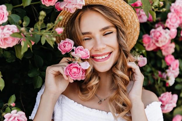 Cudowna dziewczynka kaukaski wyrażająca szczęście w słomkowym kapeluszu. ładny modelki stojącej w pobliżu krzewu różanego w letni dzień.