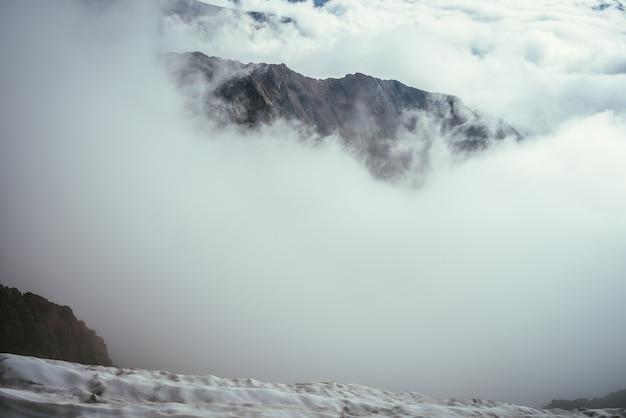 Cudowna górska sceneria ze wspaniałymi skałami w gęstych niskich chmurach. nastrojowy krajobraz górski z dużymi górami skalistymi nad chmurami. piękny widok z ośnieżonego szczytu na wysokie skały nad gęstymi chmurami.