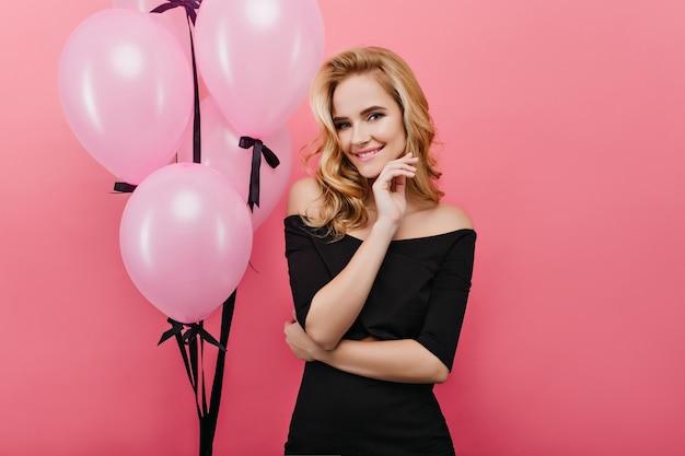 Cudowna jasnowłosa kręcona kobieta stojąca na jasnej ścianie podczas przyjęcia urodzinowego. oszałamiająca blondynka świętuje wakacje z balonami.