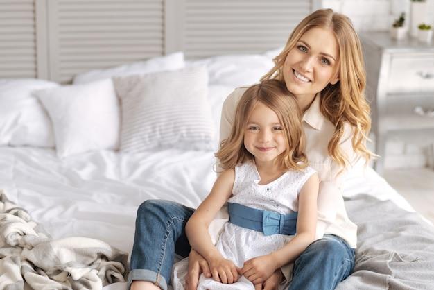 Cudowna jasnowłosa matka i jej urocza urocza córka siedzą na łóżku z dziewczyną opartą na plecach o matkę