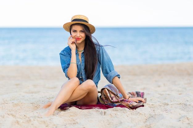 Cudowna kobieta o opalonym ciele, pełnych czerwonych ustach i długich nogach pozuje na tropikalnej słonecznej plaży. nosi krótki top, szorty i słomkowy kapelusz.