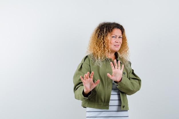 Cudowna kobieta pokazująca gest stop w zielonej kurtce, koszuli i przestraszony. przedni widok.