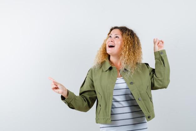 Cudowna kobieta wskazująca na lewą stronę iz powrotem w zielonej kurtce, koszuli i wyglądająca na zaskoczoną. przedni widok.