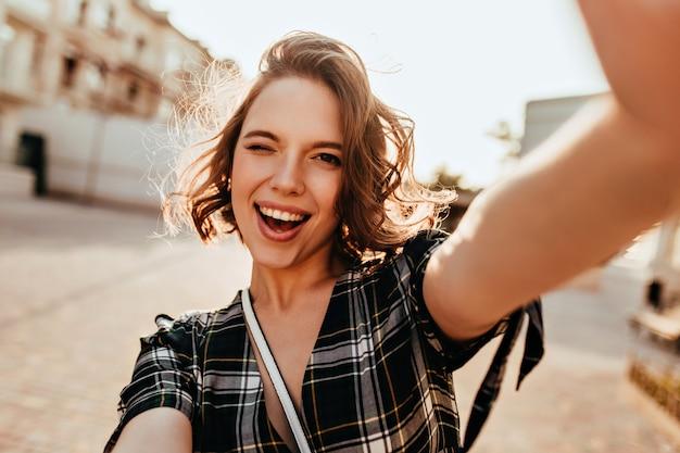 Cudowna kręcona kobieta o ciemnych oczach pozuje figlarnie na ulicy. plenerowe zdjęcie inspirowanej młodej damy robiącej selfie.