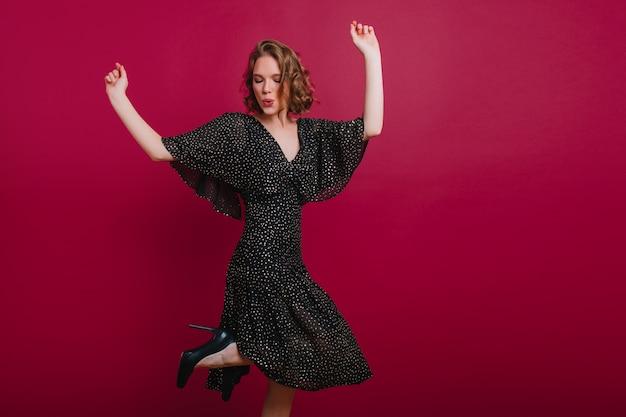 Cudowna młoda dama w sukience w kropki tańczy z rękami do góry. wyrafinowana europejska dziewczyna o ciemnych włosach słucha muzyki z uśmiechem.