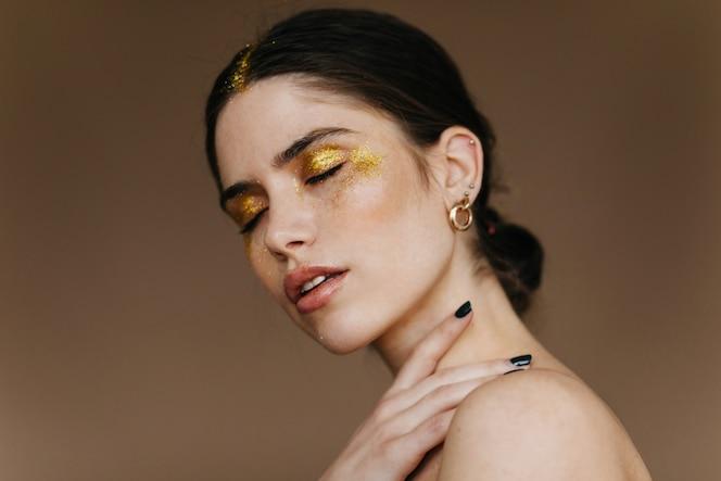 Cudowna młoda dama ze stylowym złotym kolczykiem pozuje na ciemnej ścianie. ekstatyczna brunetka kobieta z makijażem partii stojącej z zamkniętymi oczami.