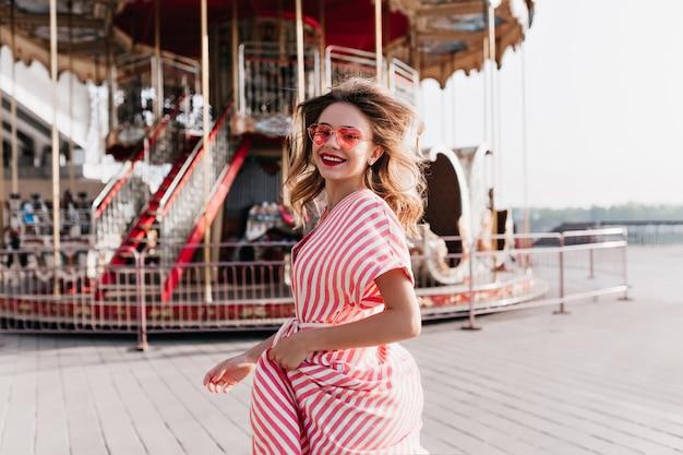 Cudowna młoda kobieta, patrząc przez ramię, pozując obok karuzeli. śmiejąca się jocund dziewczyna w okularach przeciwsłonecznych, wyrażająca szczęście w letnim parku rozrywki.