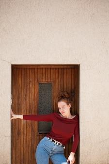 Cudowna młoda kobieta pozuje przed drzwi