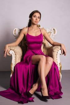 Cudowna młoda kobieta w luksusowej sukience siedzi na krześle w luksusowym apartamencie. klasyczne wnętrze w stylu vintage. piękno, moda.