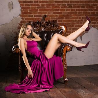 Cudowna młoda kobieta w luksusowej sukience siedzi na krześle w luksusowym apartamencie