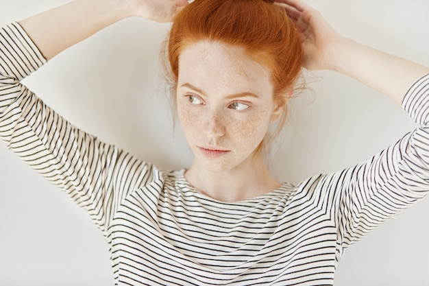 Cudowna młoda kobieta w pasiastym topie, zawiązująca rude włosy w kucyk, przygotowująca się przed pójściem na studia. piękna ruda nastolatka wygrywa piegi dostosowując fryzurę w domu