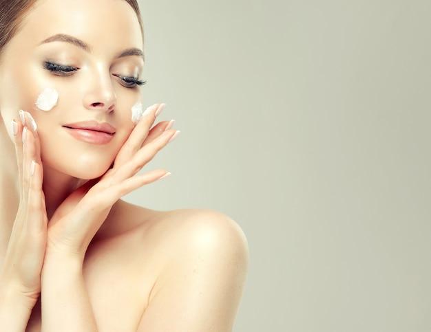 Cudowna, młoda kobieta z plamami kremu kosmetycznego na zadbanej skórze
