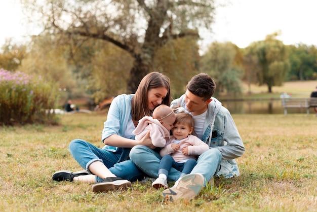 Cudowna młoda rodzina siedzi na trawie i spędza razem czas z uśmiechem.