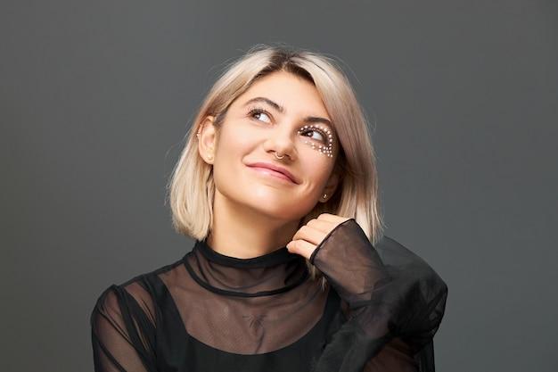 Cudowna, niesamowita młoda blondynka w przezroczystej sukience patrząca w górę z rozmarzonym wyrazem twarzy, uśmiechająca się tajemniczo i życząca sobie.