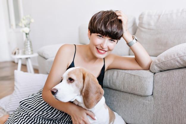 Cudowna opalona dziewczyna podpiera głowę ręką pozuje w domu po zabawnej grze z psem rasy beagle