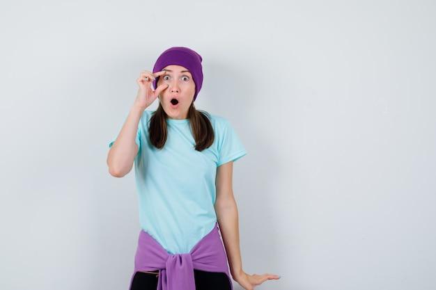 Cudowna pani otwierająca jedno oko palcami w bluzce, czapce i wyglądająca na zszokowaną. przedni widok.
