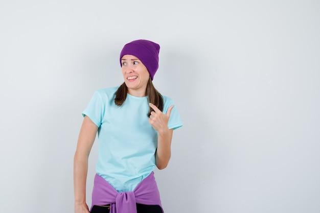 Cudowna pani wskazująca na siebie w bluzce, czapce i wyglądająca na zdziwioną, widok z przodu.