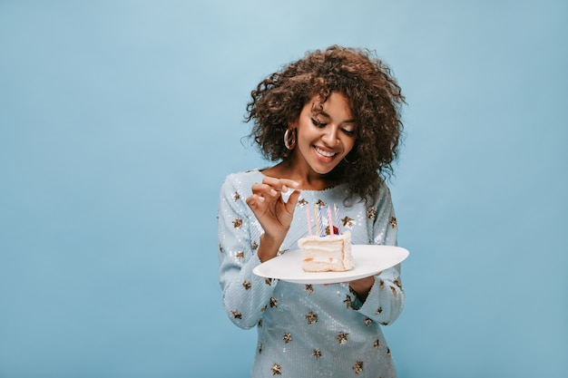 Cudowna pani z falującą stylową fryzurą w kolczykach i niebieskiej błyszczącej sukience uśmiecha się i trzyma kawałek ciasta ze świeczkami na niebieskiej ścianie..