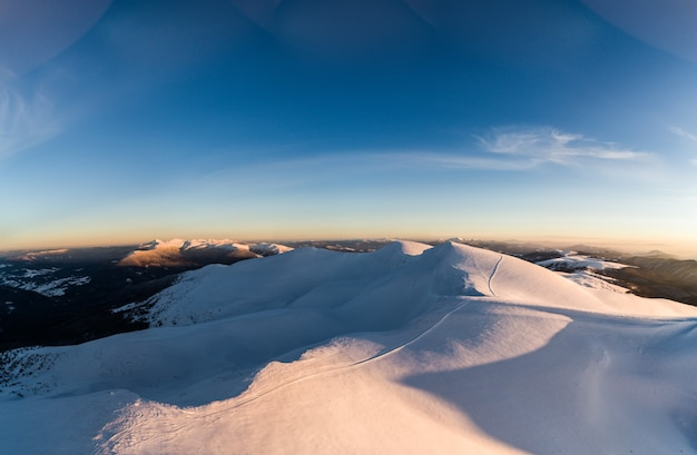 Cudowna panorama dzienna zasp śnieżnych w górach wśród lasów w słoneczny mroźny mglisty dzień