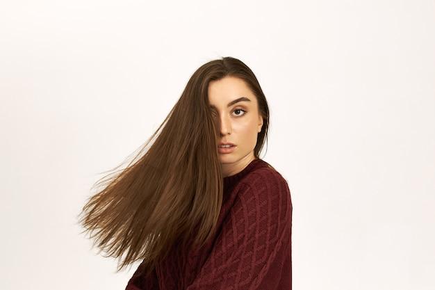 Cudowna pewna siebie młoda kobieta w ciepłym swetrze pozuje na białym tle reklamowy szampon, odwraca głowę, jej piękne lśniące włosy odlatują.