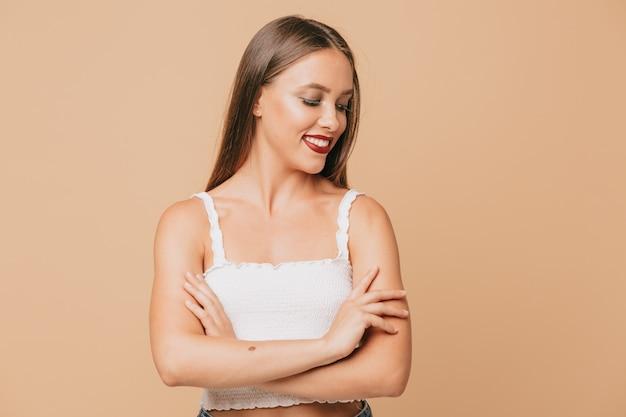 Cudowna, piękna dziewczyna z długowłosą dziewczyną uśmiechającą się nad beżową ścianą. kobieta pozuje na ścianie srebrne błyszczące girlandy
