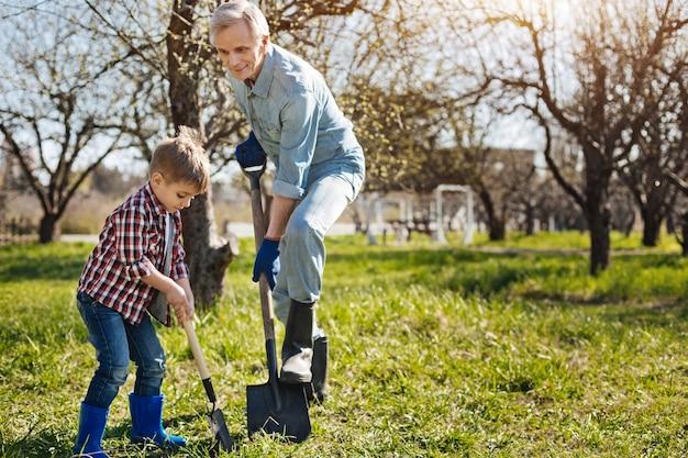 Cudowna rodzinna aktywność. dziadek w granatowych rękawiczkach ogrodowych spędza wolny czas ze swoim małym wnukiem na świeżym powietrzu podczas wspólnego ogrodnictwa