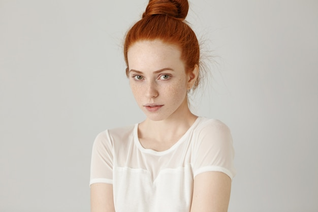 Cudowna ruda dziewczyna z węzłem włosów i piegami ubrana w białą bluzkę, lekko wzruszająca ramionami z niepewnością, patrząca, z uroczym nieśmiałym uśmiechem
