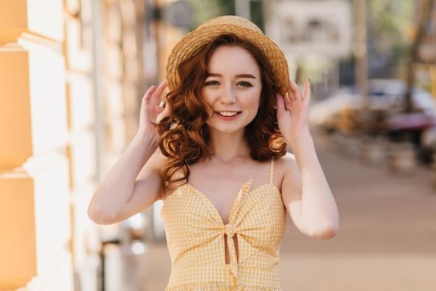 Cudowna ruda kobieta w żółtym stroju vintage idąca ulicą. odkryte zdjęcie rozmarzonej białej dziewczyny w słomkowym kapeluszu.