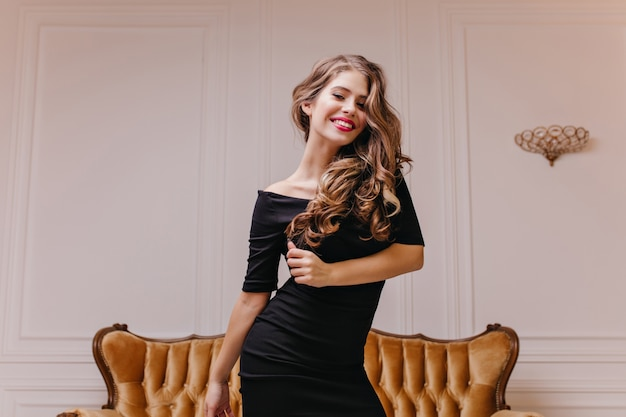 Cudowna, urocza modelka słowiańska z olśniewającym uśmiechem wyzywająco pozuje do portretu na tle białej ściany