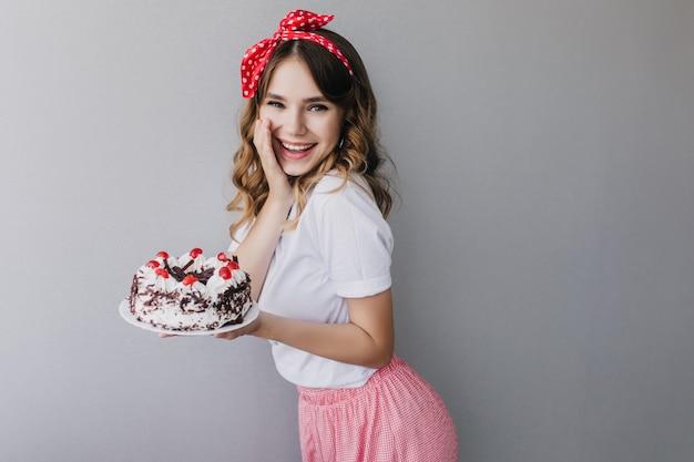 Cudowna urodzinowa dziewczyna wyrażająca pozytywne, szczere emocje. kryty strzał zadowolonej europejskiej pani w stroju vintage z słodkim ciastem.