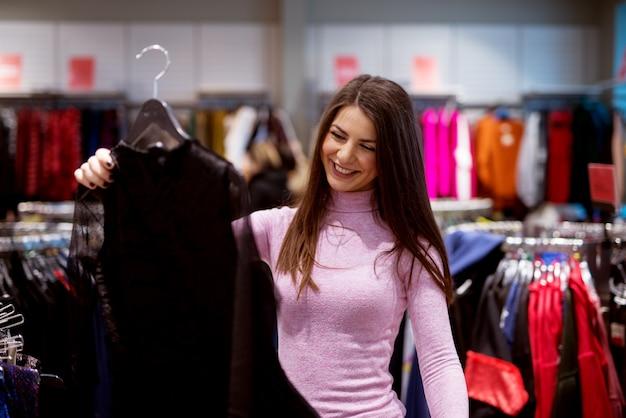 Cudowna wesoła dziewczyna cieszy się, że znalazła w sklepie sukienkę.
