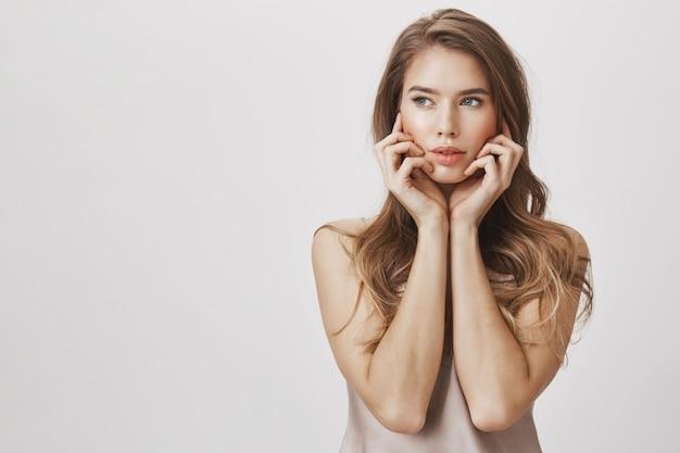 Cudowna zmysłowa kobieta wyglądająca na zamyśloną, wzruszającą twarz
