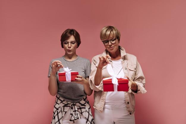 Cudowne dwie panie z krótkimi włosami w nowoczesnych ubraniach i fajnych okularach, trzymające czerwone pudełka na prezenty i rozwiązujące taśmy na różowym tle.