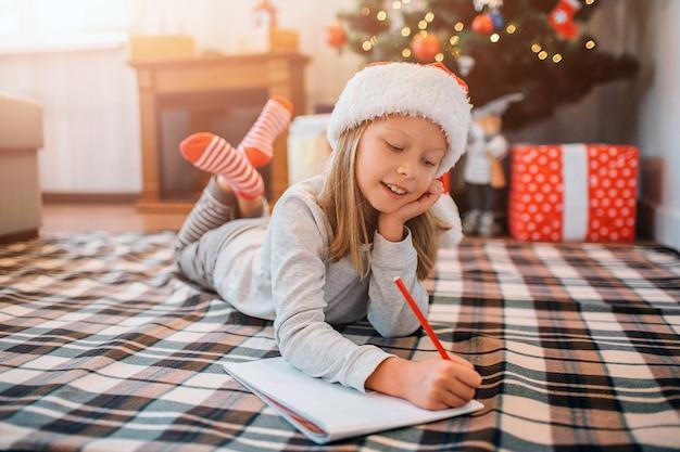 Cudowne dziecko leży na kocu i pisze list.