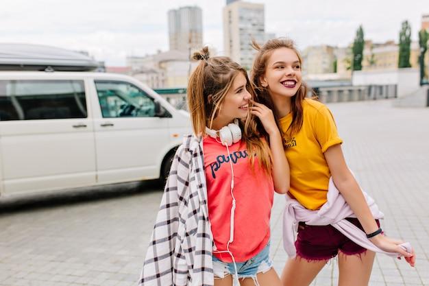 Cudowne ekstatyczne dziewczyny w letnich modnych strojach spędzają razem czas i podziwiają widoki miasta w pobliżu białego samochodu