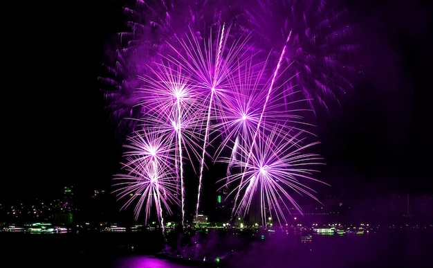 Cudowne fioletowo-różowe fajerwerki eksplodujące na nocnym niebie nad miastem